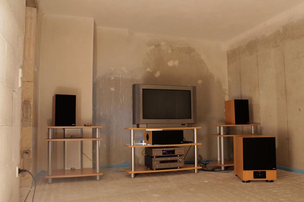 Lautsprecher und Fernseher in einem unverputzten Raum mit kahlen Betonwänden