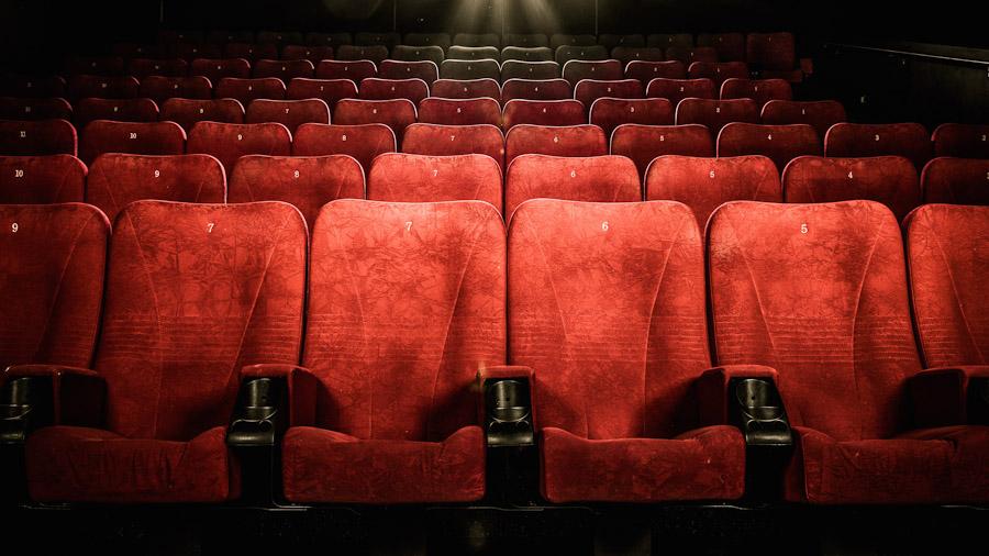Rote Kinosessel in einem Kino, mehrere Sitzreihen hintereinander.