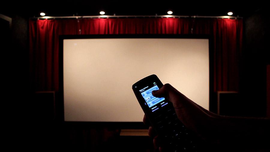 Universalfernbedienung mit dem Daumen auf dem Filmstart-Makro vor der Leinwand eines Heimkinos.