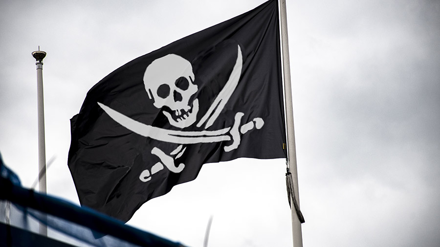 Eine Piratenflagge vor bedecktem Himmel.