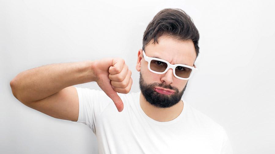 Junger Mann mit Bart und 3D-Brille hält den Daumen nach unten und schmollt.