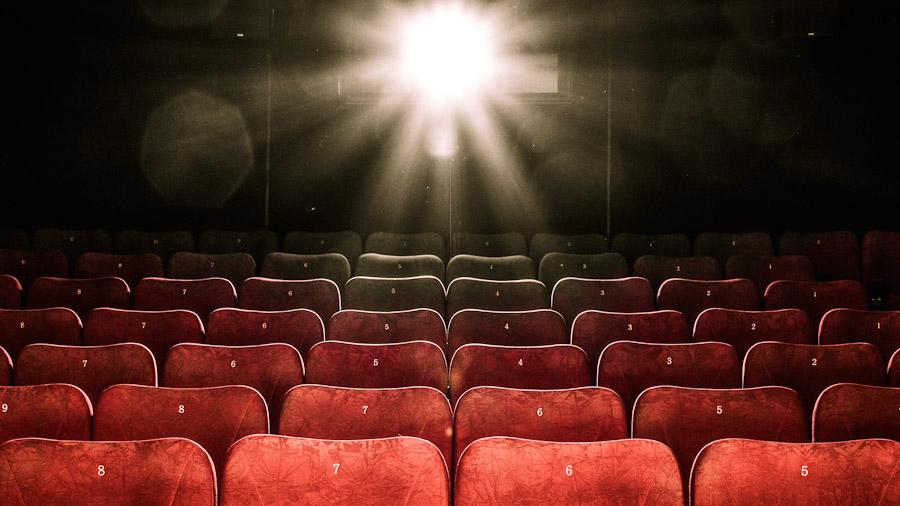 Die Rückwand eines Kinos, Sitzreihen im Vordergrund, durch die der Projektor das Bild aus dem Projektionsraum wird.