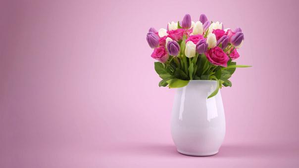 Blumenvase mit Blumen in weiß, pink und lila vor einem rosanen Hintergrund