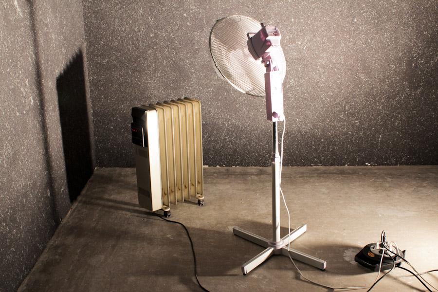 Eine mobiles Heizgerät und ein Ventilator vor einer mit Baumwollputz verkleideten Wand.