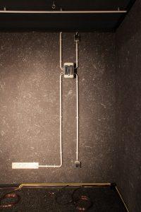 Die Front-Wand mit verschiedenen Kabelkanälen, Schaltkasten und Steckdosen