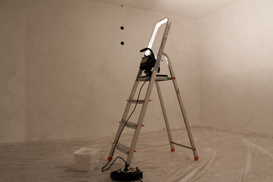 Leerer Kellerraum mit grundierten Wänden und Folie auf dem Boden ausgelegt. In der Mitte steht eine Leiter mit Baustrahler.