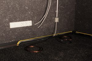 Verschiedene Kabel in den Kabelkanälen am Boden