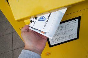 Einwurf eines Videobuster-Versandumschlags in einen Briefkasten.