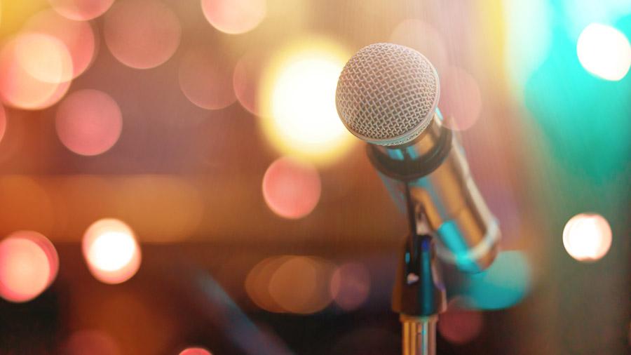 Nahaufnahme eines Mikrofons mit funkelnden Lichtern im Hintergrund.