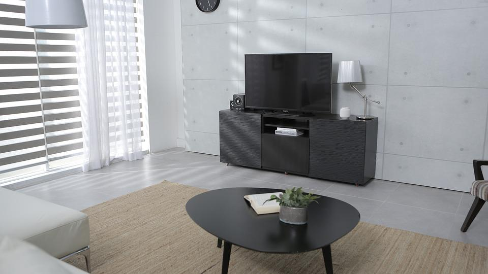 Modern eingerichtetes Wohnzimmer mit großem TV auf einem Sideboard.