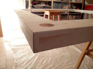 Nach dem Grundieren wird das Deckensegel erneut angeschliffen, wobei das Holz teilweise wieder sichtbar wird.