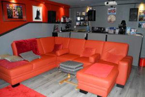 """Der Sitzbereich des Heimkinos """"VIP Lounge"""" mit rotem Sofa und Filmsammlung im Hintergrund."""