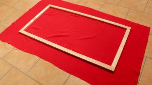 Stoff liegt auf dem Boden, der Holzrahmen mittig darauf.