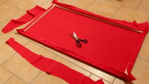 Überschüssiger Stoff wird mit einer Schere abgeschnitten, bis der Rahmen von hinten fast wieder sichtbar wird.
