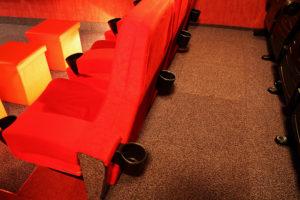Kinosessel der 1. Sitzreihe mit Getränkehaltern für die 2. Reihe