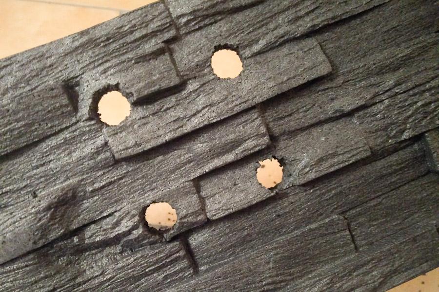 Vier Löcher für die runden Ecken einer Steckdose in der Frontansicht eines Styroporverblenders.