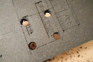 Vier Löcher für die runden Ecken einer Steckdose in der Rückansicht eines Styroporverblenders.