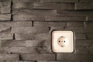Steinverblender aus Styropor an der Wand mit einer einzelnen Steckdose.
