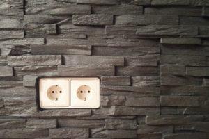 Steinverblender aus Styropor an der Wand mit einer Doppelsteckdose.