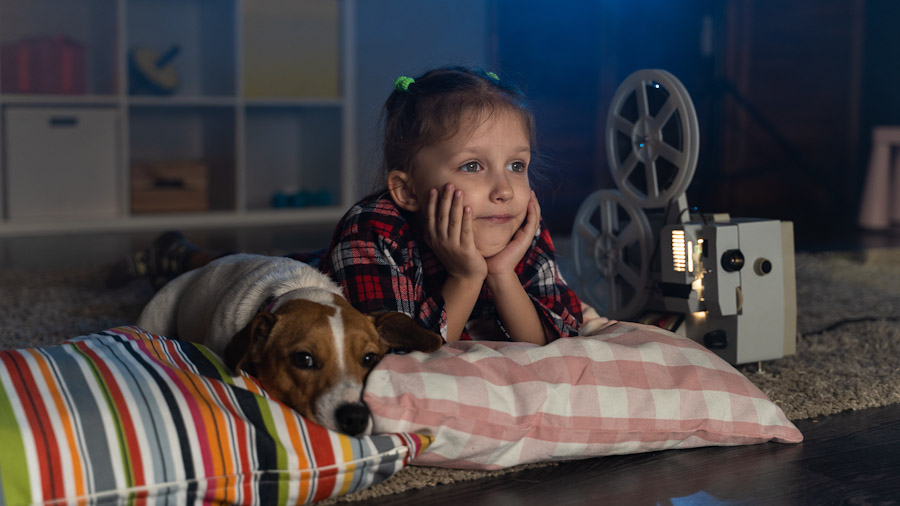 Ein Mädchen liegt auf einem Kissen und schaut einen Film über einen analogen Filmprojektor.