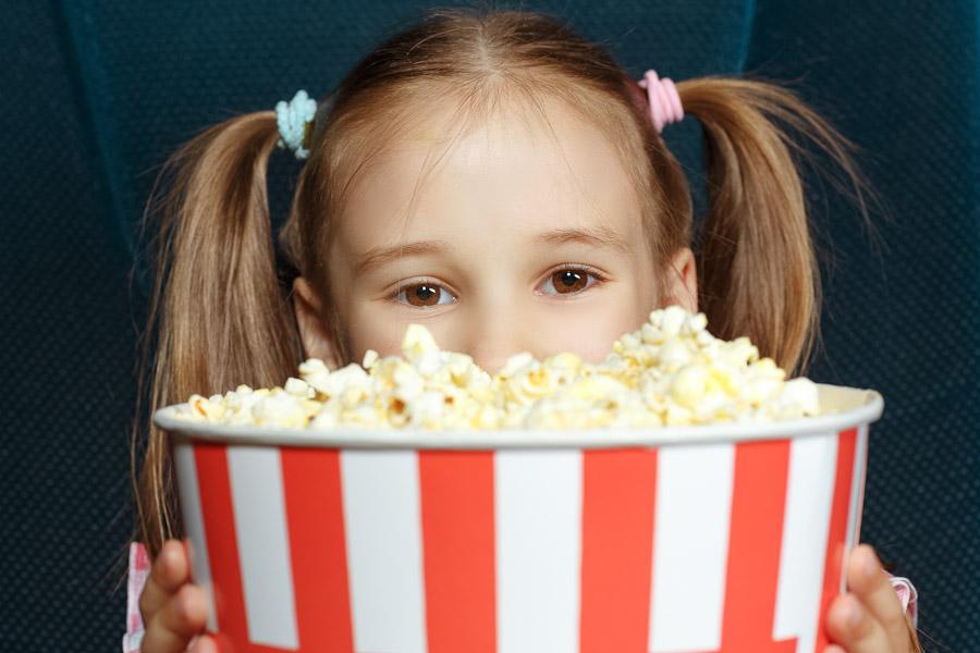 Ein Mädchen sitzt in einem Kinosessel und schaut über den Rand ihres Popcorn-Eimers.
