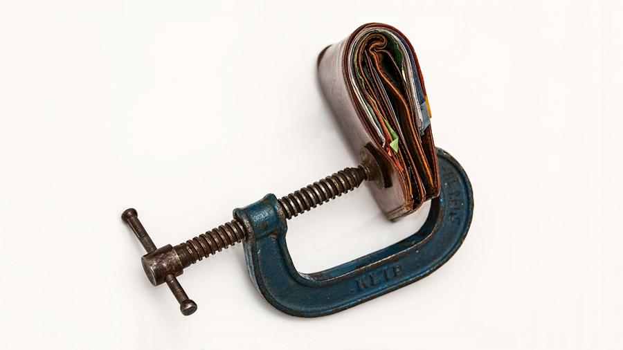 Geldbeutel im Schraubstock – Symbolfoto für Ratenkauf und Finanzierung