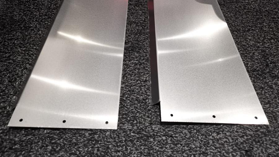 Zwei Aluminium-Maskierungsbretter im Rohzustand. An den Enden sind Löcher für die Befestigung vorgebohrt. Eine abgeschrägte Kante auf einer Seite neigt sich später zur Leinwand hin und verhindert so Schattenwurf.