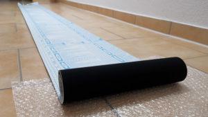 Eine 30 cm breite Rolle schwarze Velour-Folie, teilweise auf dem Boden ausgerollt.