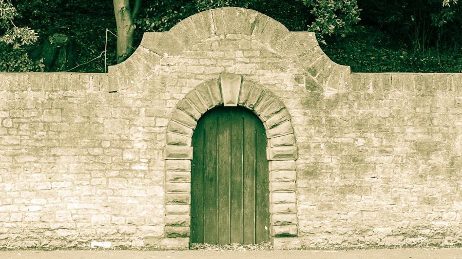 Ein antiker Torbogen in einer Mauer, bei dem deutlich der trapezförmige Schlussstein an der Spitze des Bogens zu erkennen ist.