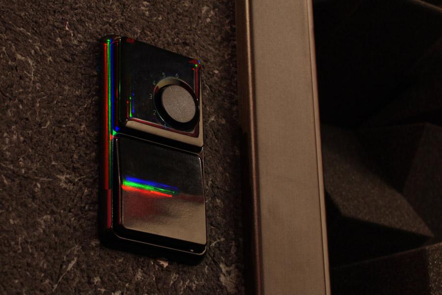 Ein Bild meins Lichtschalters, schwarz auf dunkler Wand. Der Regenbogeneffekt wird an hellen Lichtreflexionen sichtbar, die normalerweise weiße Spots im Bild sind.