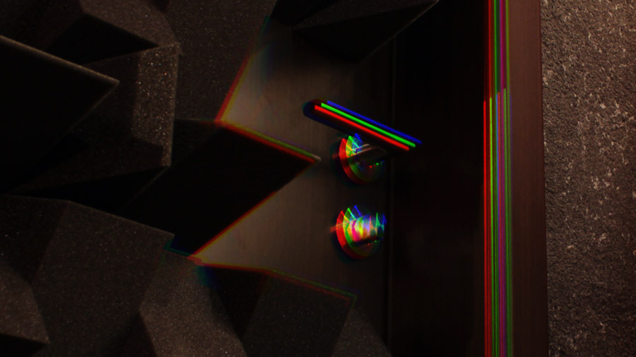Ein Bild meiner Türklinke, Edelstahl auf dunklem Holz. Der Regenbogeneffekt wird an hellen Lichtreflexionen sichtbar, die normalerweise weiße Spots im Bild sind.