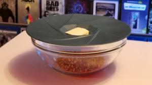 Popcorn-Deckel aus Silikon auf einer Glasschüssel. In der Schüssel befindet sich Popcornmais, in der Mulde auf dem Deckel befindet sich ein Stück Butter.