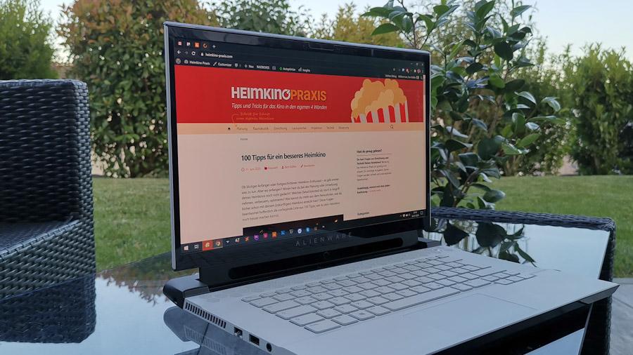 Ein Notebook auf dem Gartentisch zeigt die Startseite von Heimkino Praxis an.